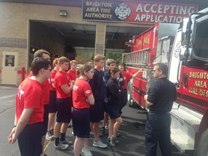 Students at fire hall examining fire truck